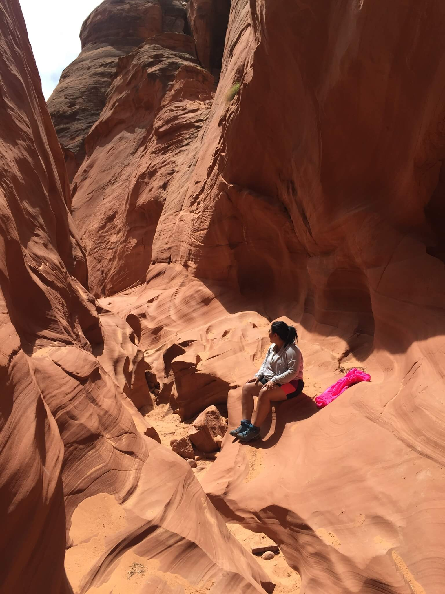 Val sits on red rocks during a hike
